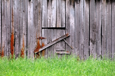 Background image shows rustic, wooden barn surrounded by tall green grass.  Entrance is closed and barred. photo