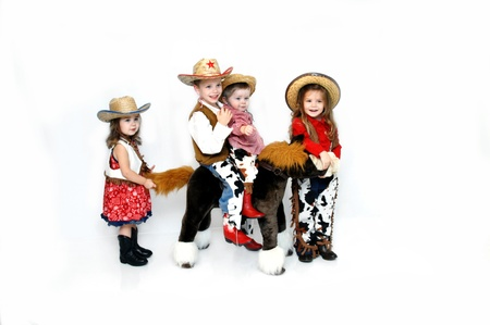 Family of four dress up for Halloween as cowboys and cowgirls.  The boys are riding a stuffed pony and the girls are leading and bringing up the rear. Stock Photo