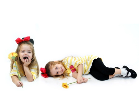quietly: Double image of adorable little girl shows her in two situations.  One is quietly laying on the studio floor holding her flower.  The other shows her laughing and sitting up. Stock Photo