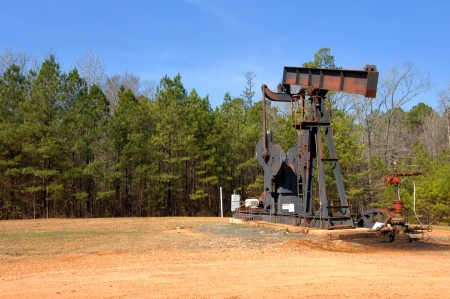 oil well: Arkansas oil well sits idle surrounded by pine trees and blue sky. Stock Photo