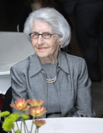 Female senior sits at restauraunt table.  She is classy and wearing a grey suit with pearls.  She is sitting serenely waiting for her food.