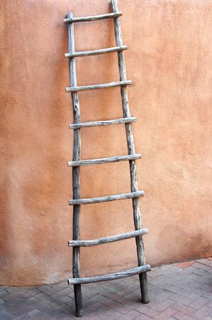 Old ladder leans against the wall of an adobe shop in