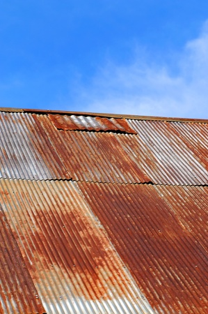 rusting: Old corrugated tinroof is rusting and patched.  Sunny blue sky and whispy clouds frame building.