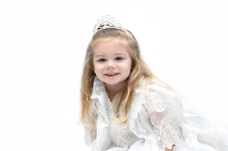 dressup: Little girl wears an elegant wedding dress and crown.  She is sitting in an all white room and smiling happily as she dreams of her getting married when she grows up.