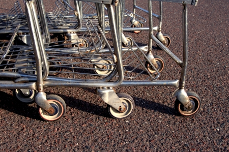 shopping buggy: Stack of grocery cars sit on rough pavement of grocery story parking lot.  Grocery carts take much abuse from being tipped over, run over, left outdoors and rough pavement.