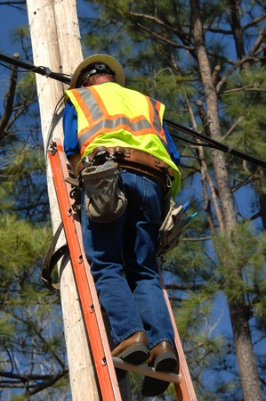 Employee works on power line on a sunny day with blue skies.  He is wearing safety equipment including belt and neon vest.