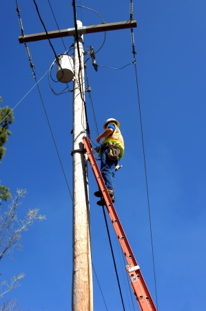Repairman works on telephone and cable lines on a high telephone pole.  He is standing on a 30 fooot ladder and wearing safety belt, safety vest and hard hat.