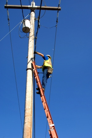 to climb: High risk worker stands on a 30 foot ladder and repairs telephone lines and cable communication troubles.  Vivid blue sky frames worker standing on ladder.