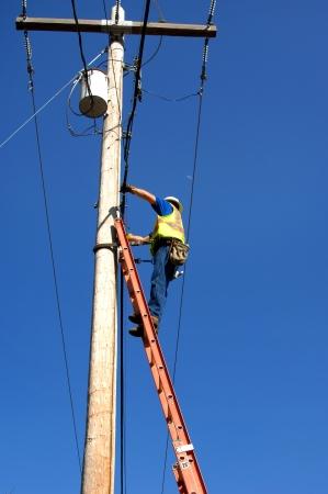 Hoog risico werknemer staat op een 30 voet ladder en reparaties telefoonlijnen en kabel communicatie problemen. Levendige blauwe hemel frames werknemer staande op ladder.
