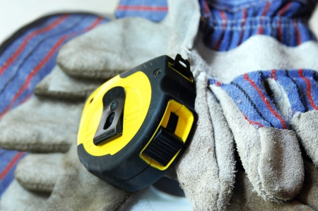 Bright yellow tape measure lays across a pair of dirty work gloves. Stock Photo - 14863905