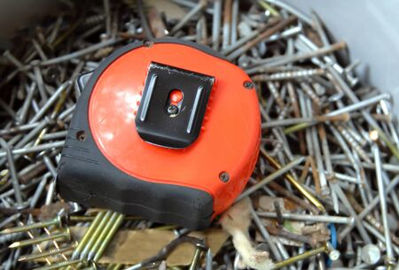 Bucket of nails and screws are topped by a bright orange tape measure. photo