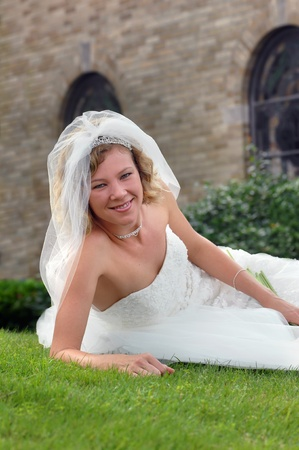 Bride lays on the grass in front of the church were she will be married.  She is smiling and radiant. photo