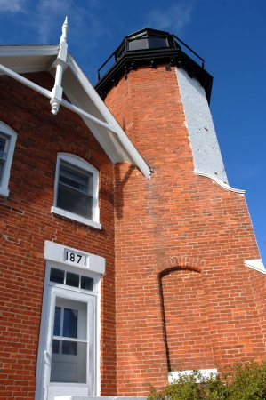 Entrance to Eagle Harbor lightkeepers home, connected to lighthouse, was built in 1871 according to plaque over doorway.  Vivid blue skies over Upper Peninsula, Michigan frame dwelling and light.