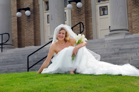 Beautiful bride relaxes on the grassy lawn in front of the church.  She is barefoot and holding her bouquet of calalilies.