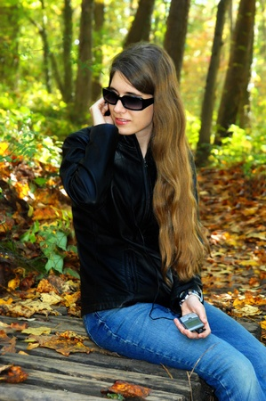 Teenager, wearing black leather jacket and sunglasses, listens to her music with the aid of ear plugs.  She is surrounded by fall foliage at an Asheville, North Carolina park. Standard-Bild