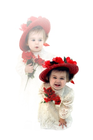 chuckling: Gorgeous little girl laughs hilariously and bends over double   She is dressed in an ivory lace dress, red straw hat with silk roses and is holding red silk roses   Second image shows thoughtful child dressed the same looking in identical outfit  Stock Photo