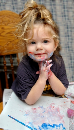 Adorable little girl poses besides her masterpiece   She has paint smeared on her face and hands  Stock Photo