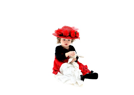 rag doll: Little girl plays with old fashioned rag doll and wears old fashioned red, straw hat with red silk roses and net   She is sitting in an all white room and clutching her doll
