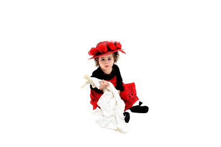 velvet dress: Little girl sits in all white room holding an old fashioned rag doll and wearing an old fashioned straw hat topped with red roses and net   Her dress is black velvet and red tulle with embrodiery in black