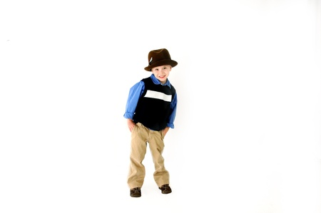 khakis: Little five year old boy poses with a derby hat   He is wearing khakis and sweater vest and smiles naturally l