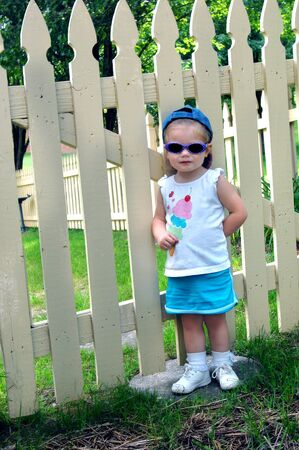 Little girl wearing sunglasses and a cap turned backwards, stands besides a wooden picket fence  Stock Photo