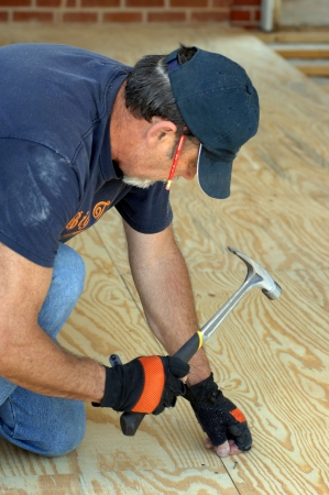 Carpenter hammers plywood on the floor of new home.  He has a pencil behind his ear.