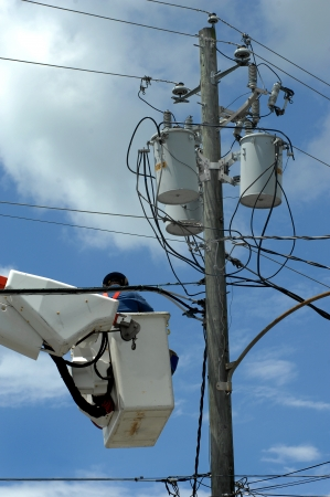 Electric serviceman works on a conglomeration of wires near voltage boxes on a telephone pole.