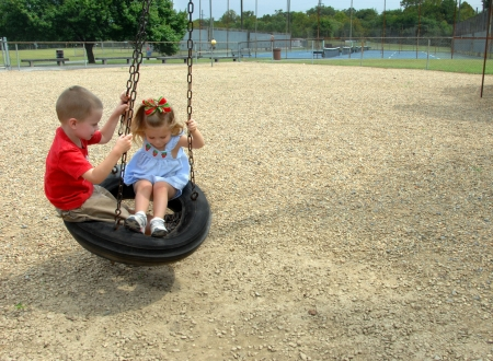 tire: Brother and sister swing together on a tire swing.  They are playing at a city park on a summer afternoon.