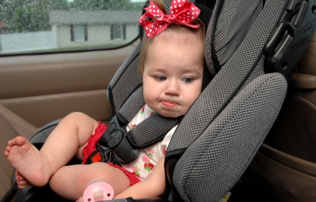 Infant sits in a car seat buckled up for safety.  She is making a funny face as this is not her favorite place to be. photo