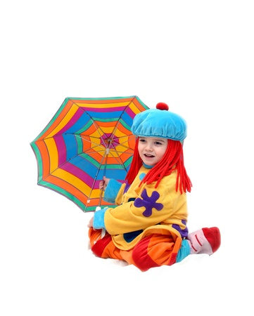 Little boy enjoys playing clown for the day.  He has umbrella in bright colors and hair in bright red. photo