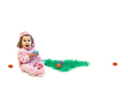 Little girl sits in an all white room hunting Easter Eggs.  She is wearing a pink bunny costume and holding an egg. photo