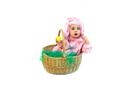 Pink Easter bunny finds an yellow egg in the extra large Easter basket that she is sitting in.  She is wearing a pink rabbit costume. photo