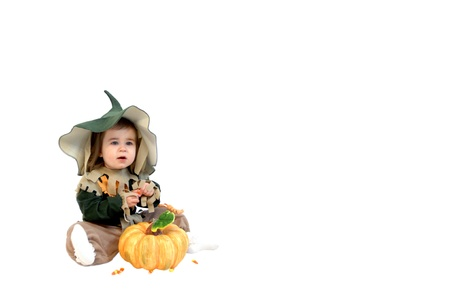 Cute little scarecrow, complete with hat, picks up a piece of candy corn to pop into her mouth.  Small pumpkin sits in front of her. photo