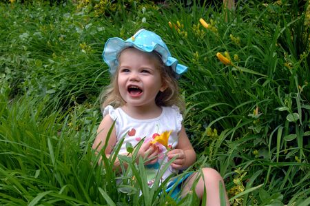 Small child yells as a yellow spring flower showers her nose with yellow pollen.  She is wearing a turquoise and white dotted hat. photo