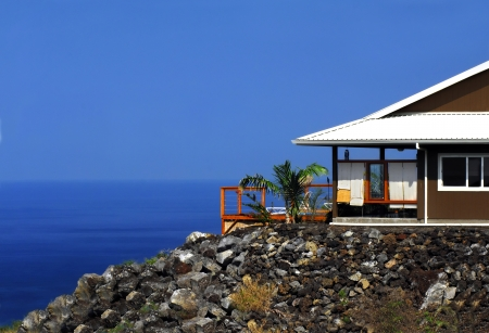 Home in Milolii Village has unobstructed view of the ocean and horizon.  Home has patio with lawn chair. Stock Photo
