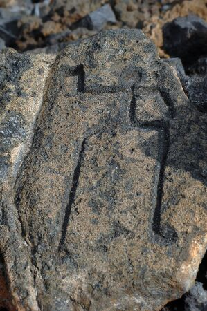 Petroglyphs drawn by early Hawaiian depicts a man scratched on a large stone.  Big Island of Hawaii petrophys. photo