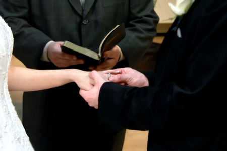 sealing ring: Groom holds brides hand during wedding ceremony as he places his ring on her finger.  Pastor stands behind holding a Bible. Stock Photo
