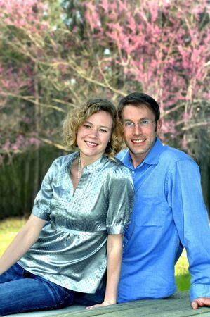 Young couple sit on a wooden porch.  They are surrounded in the background by blooming pink dogwood.  Both are dressed casual and smiling. photo