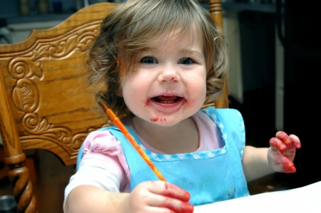 smeared: Toddler beams with enthusiasm as she takes her first art lesson.  She has paint smeared on her face, hands and even in her hair.