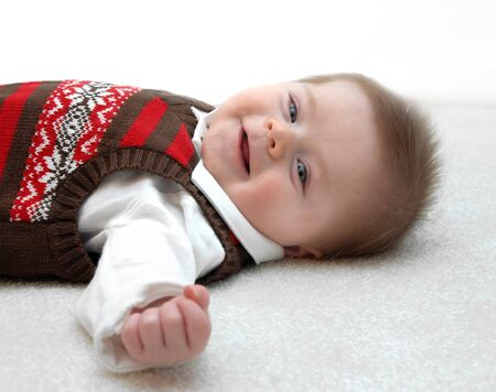 contented: Innocent little baby lays on the white carpet of his home   He is smiling and contented    Stock Photo
