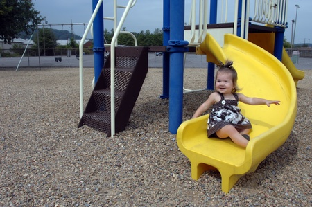 Little girl takes a turn on a yellow slide all by herself   She is smilng in pleasure with arms extended for balance  photo