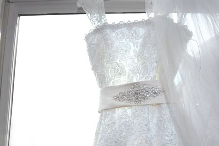 Elegant window dressing bedazzles the frame with sequins, bling and an ivory sash  Bridal gown hands from window facing  Stock Photo