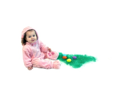 Baby girl is dressed in a pink bunny costume   She is sitting besides a bed of Easter grass and Easter eggs  photo