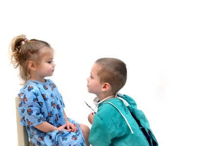 Two little children play doctor.  The little girl is the patient and the little boy is the physician.  He is holding an instrument and beginning the examination.