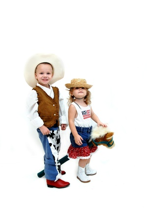 Two small children play dressup western style complete with stick pony   Little boy is smiling big  photo