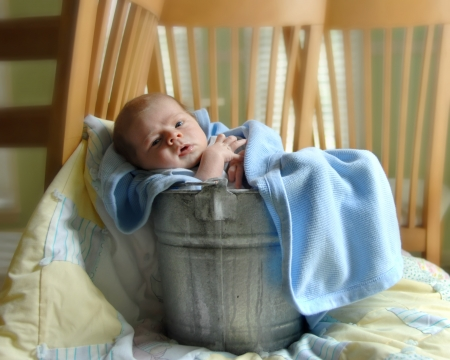 swaddled: Tiny baby relaxes in a rustic aluminum pail swaddled in blankets   He is awake and looking around his new home