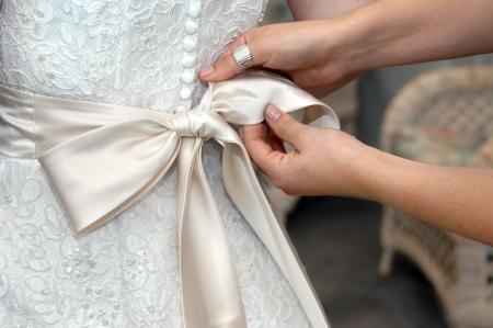 Handen te binden de satijnen strik van huwelijkstoga Close-up van vrouwelijke handen lus banden in een elegante boog Stockfoto