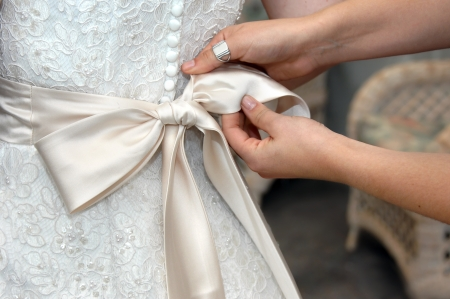 Hands tie the satin bow of wedding gown   Closeup of female hands looping ties into elegant bow  photo