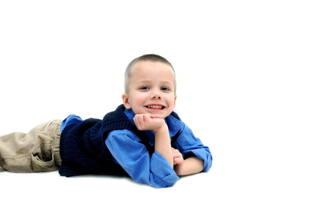 khakis: Small boy lays on an all white floor and smiles happily   He is wearing tan khakis and a navy sweater vest  Blue shirt has sleeves rolled up to the elbows