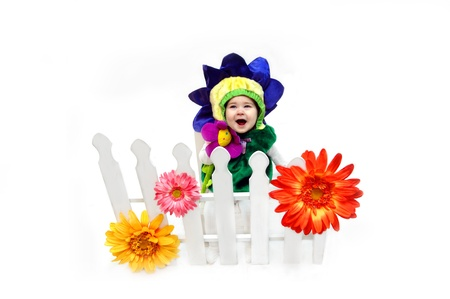 Baby girl, dressed in flower costume, sits behind a white picket fence where she is planted   She is laughing and blossoming as she clutches her plush flower   Huge flowers in yellow, pink and orange grow between the white wooden slats  Stock Photo - 14910041